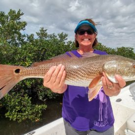 a picture of a fisherman holding a large backcountry redfish she caught.