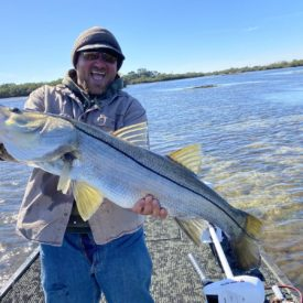 a picture of a fisherman holding a snook caught on a very shallow flat in Crystal River