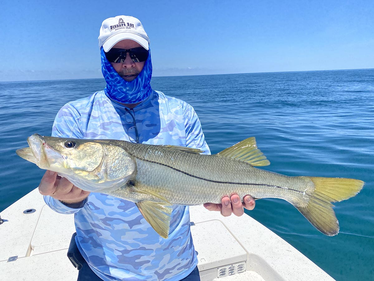 a picture of a fisherman with a snook he caught on a crystal river fishing charter