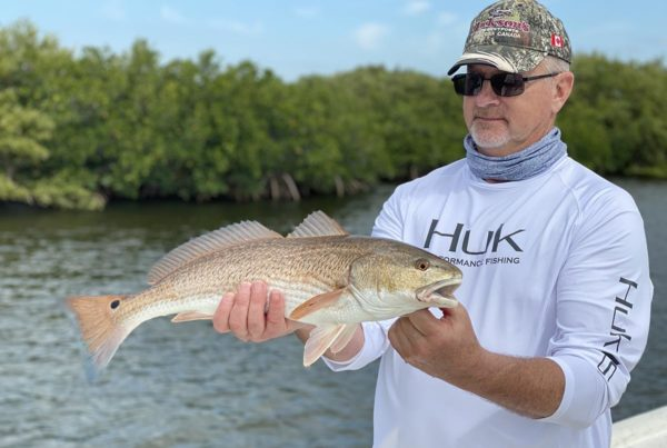 a picture of a fisherman holding a redfish he caught on a crystal river fishing charter.