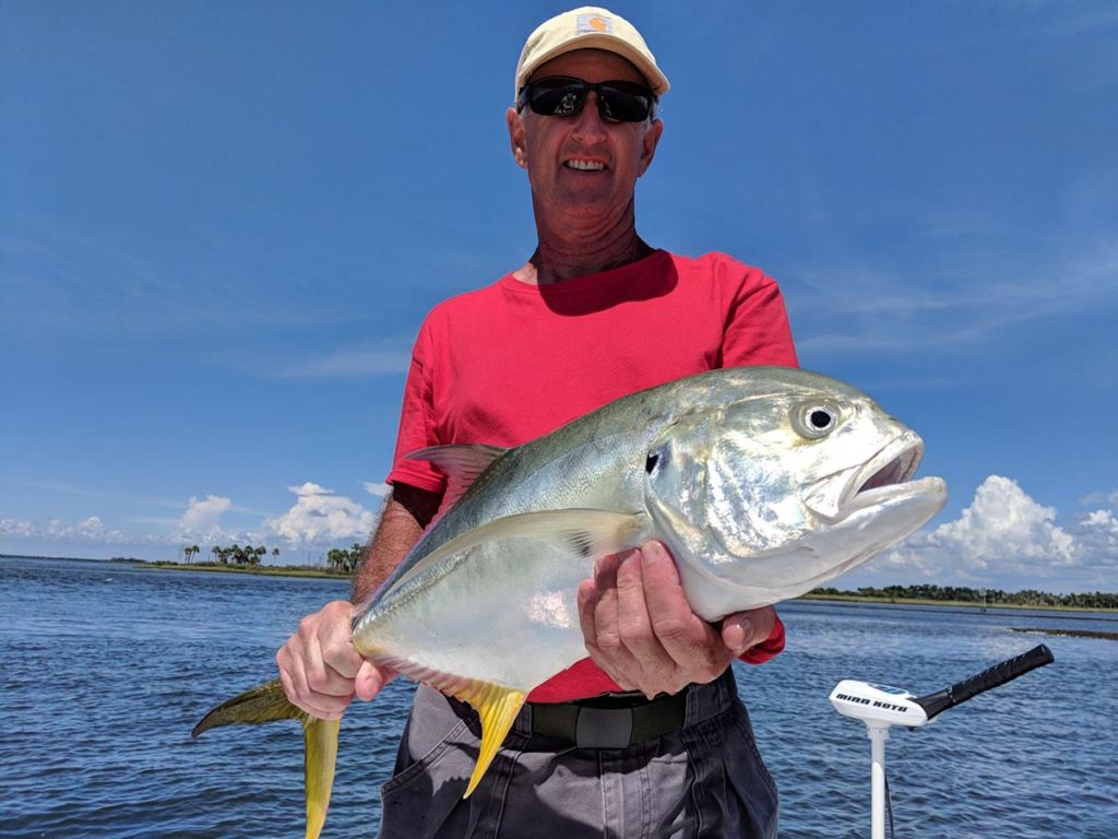 a fisherman holding a large jack crevalle he caught on a crystal river fishing charter.