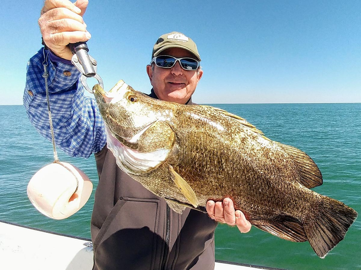 a fisherman holding a tripletail he caught