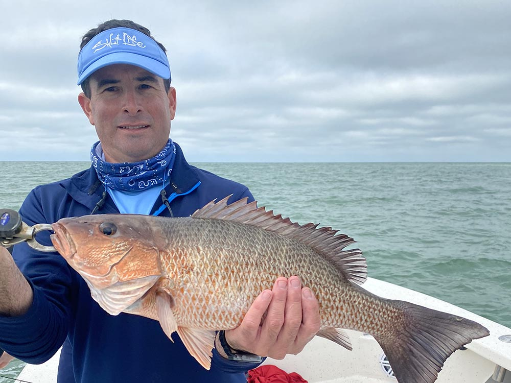a crystal river fishing charter client holding a snapper